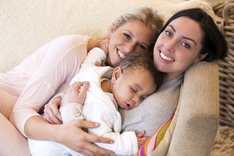 two moms so happy that their night weaned baby is asleep